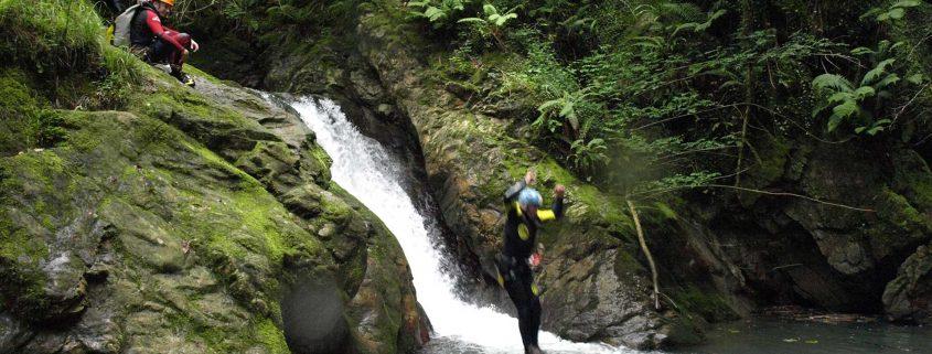 Joven saltando a poza de río en la actividad de barranquismo