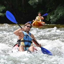 Un hombre en la canoa en un tramo donde hay un rápido