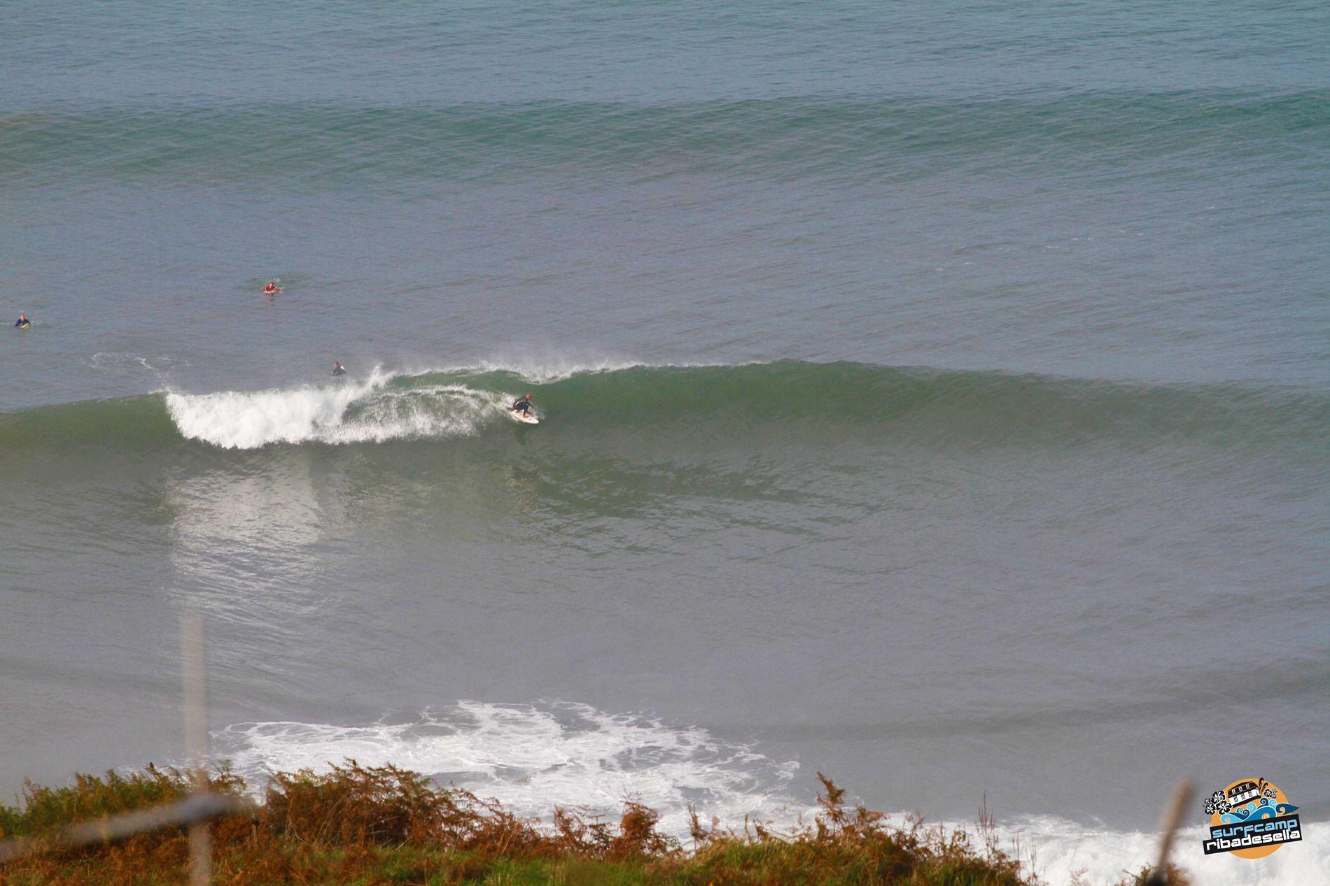 Cogiendo una ola con la tabla de surf en una playa de Asturias